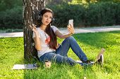 Woman Relax With Headphones Listening To Music Sitting On Grass In Park. Young Woman Enjoys Music An poster