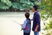 Father with son fishing at river bank, summer outdoor. Man and young boy standing at river bank with poster