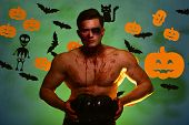 Monster With Blood On Face And Chest Holds Black Pumpkin. Man With Serious Face And Naked Torso On G poster