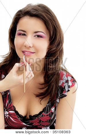 Portrait of beautiful young woman with esthetician applying lipstick on her lips