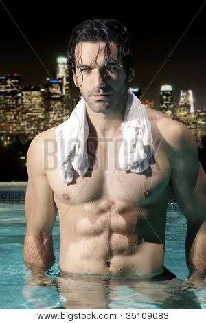 Sexy male model with great abs and muscular body in swimming pool at night with city skyline background