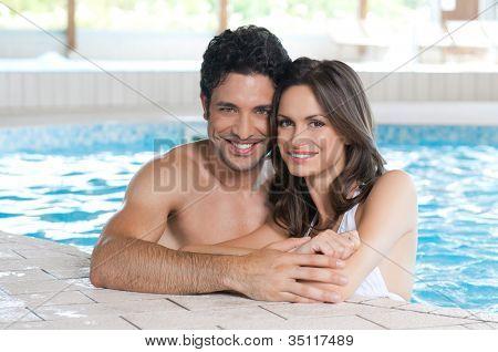 Feliz pareja sonriente mirando a cámara mientras se relaja en el borde de una piscina
