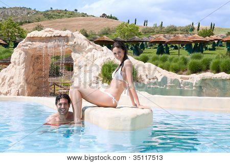 Feliz sonriente pareja joven relajándose en la piscina de un resort