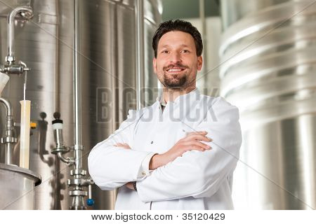 Brewer standing in his brewery in front of a stainless copper fermenter
