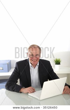Smiling Senior Businessman At His Desk