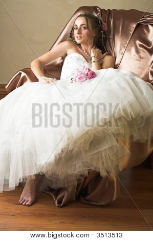 Bride With Brown Long Hair Sitting In Chair