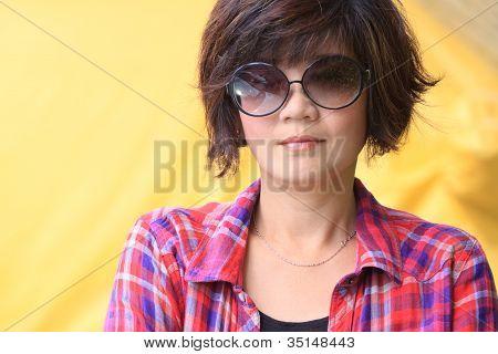 asiatische Frau mit Augen Brille und rot-gelb karierte Hemden-Hintergrund