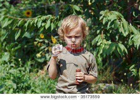 süße junge Blasen einen Blasen im Freien an einem sonnigen Tag