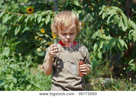 Young blond boy playing with bubbles outdoors on a sunny day