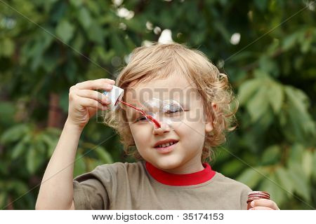 Little boy playing with bubbles outdoors