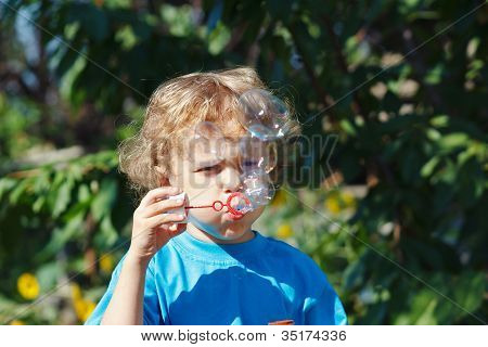 Cute boy playing with bubbles outdoors on a sunny day