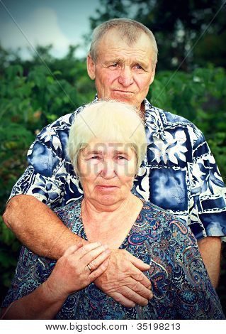 Sad Senior Couple Embracing Outdoors
