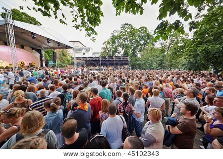MOSCOW - JUN 23: People at concert of Chaif rock-band at outdoor performance stage during VII traditional festival of live sound Music of Summer in Hermitage Garden, Jun 23, 2012, Moscow, Russia.