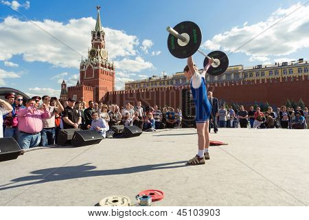 MOSCOW - MAY 26: Young athlete raises the barbell on VIII Forum Ready for Labor and Defense on May 26, 2012 in Red Square, Moscow, Russia.