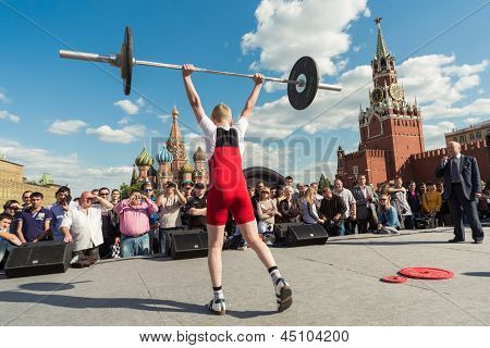 MOSCOW - MAY 26: Young athlete in red raises the barbell on VIII Forum Ready for Labor and Defense on May 26, 2012 in Red Square, Moscow, Russia.
