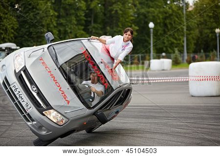 MOSCOW - JUN 30: Stuntmen from team Avtorodeo Togliatti Trick performance during Speedfest at Olympic complex Luzhniki, man drives and woman lies on roof, June 30, 2012, Moscow, Russia.