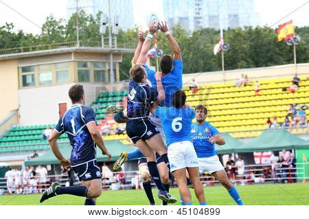 MOSCOW - JUN 30: Athletes fight for ball at second stage of European championship on rugby-7 in sports complex Luzhniki, Jun 30 2012, Moscow Russia. Athletes from Italy in blue, from Scotland in black