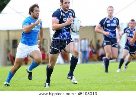 MOSCOW - JUN 30: Athlete runs with ball at second stage of European championship on rugby-7 in sports complex Luzhniki, Jun 30, 2012 Moscow, Russia. Athletes from Italy in blue, from Scotland in black