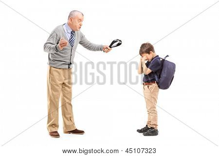 Full length portrait of an angry grandfather holding a belt and shouting at his nephew isolated on white background
