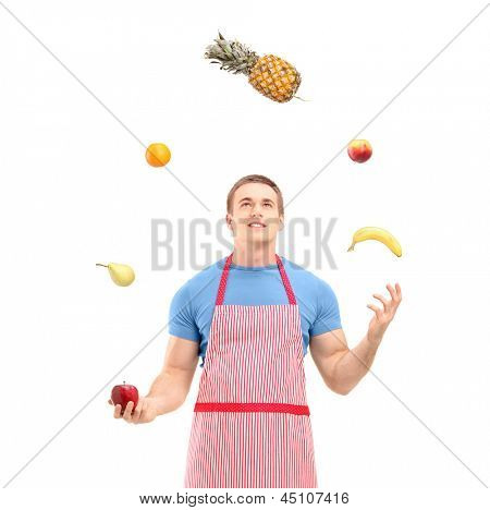 Young man in apron juggling with fruits, isolated on white background