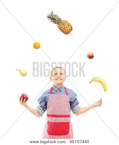 A boy with apron juggling with fruits isolated on white background