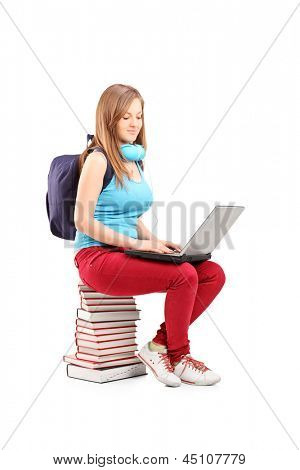 A smiling student with backpack typing on a laptop and sitting on pile of books, isolated on white background