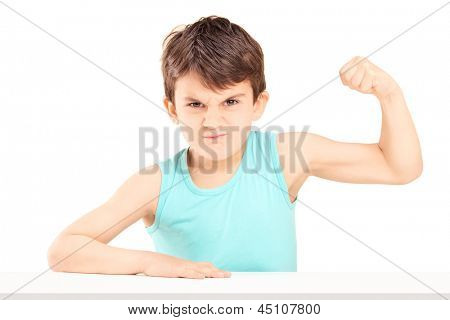 A mad child showing his muscles seated on a table isolated on white background