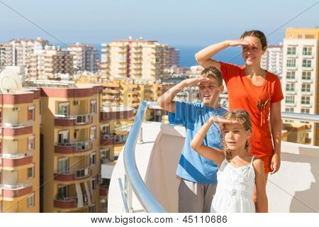 Family of three on the balcony of the room at the hotel looking into the distance on the top floor