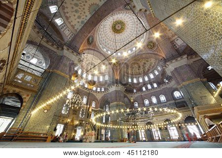 People inside grand, beautiful and old New Mosque (Yeni Cami) in Istanbul, Turkey. Central dome has height of 36 m and diameter of 17.5 m.