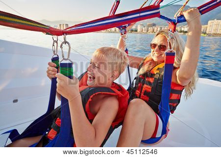 Mother and her son sit in moving motorboat and ready to soar and paraglide, focus on mother