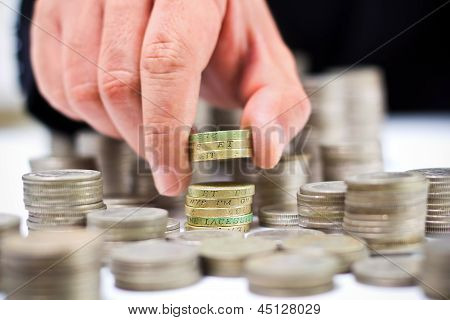 Closeup Of Stack Of British Pound Coins With A Male Hand