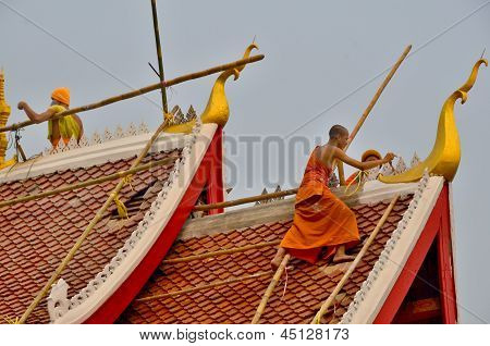 Monks works to resurface the roof and repaint their pagoda
