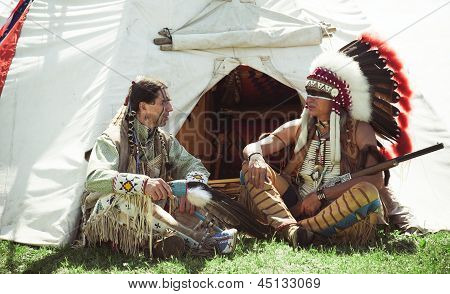 North American Indians sit at a wigwam