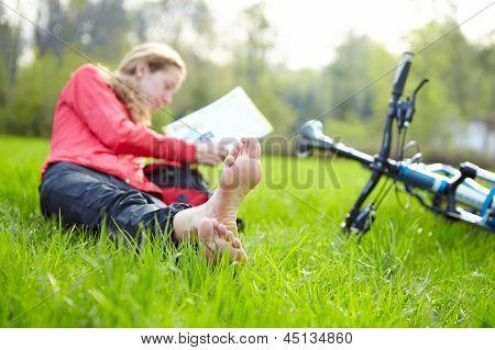Girl Cyclist On A Halt Reads Lying In Fresh Green Grass Barefoot
