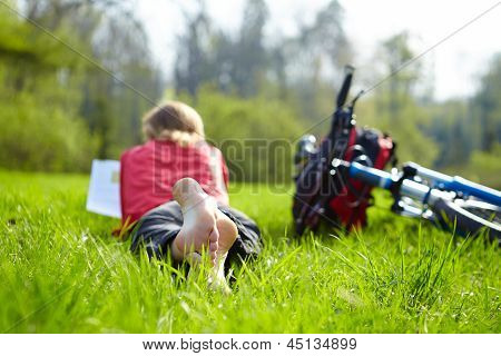 Girl Cyclist On A Halt Reads On Green Grass Outdoors In Spring Park