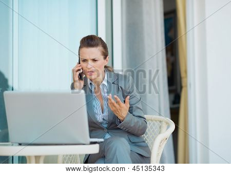 Concerned Business Woman Talking Cell Phone On Terrace