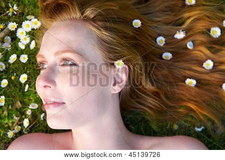 Portrait Of A Beautiful Woman Lying On Grass With Flowers In Hair