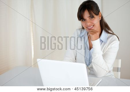 Charming Young Woman Looking At You Using Laptop