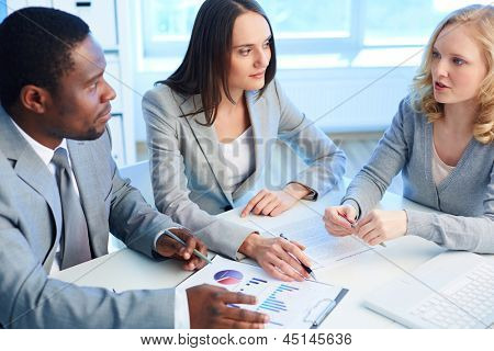 Two employees listening to the business partner while working with papers at meeting
