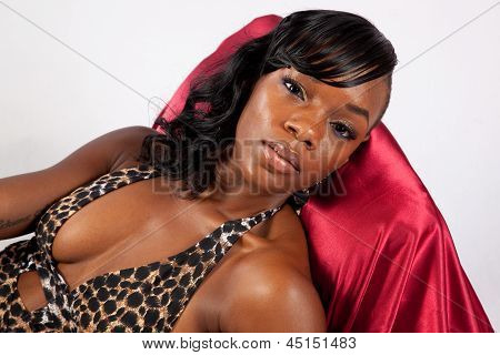 Black young woman reclining on red