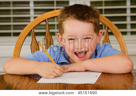 Happy child doing his homework at kitchen table at home