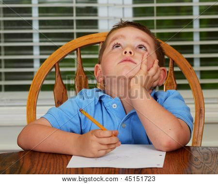 Thoughtful child doing his homework at kitchen table at home