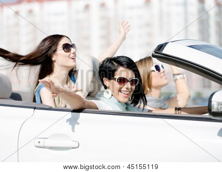 Group of happy girls with outstretched arms in the car. Little trip of teenage ladies