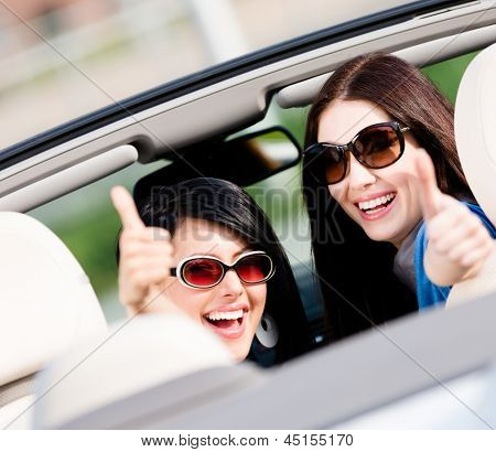 Two happy girls sitting in the car and thumbing up turn back and have fun while having little car trip