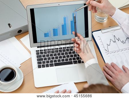 Business people discussing graphs on the laptop sitting at the table. Close up of hands and laptop