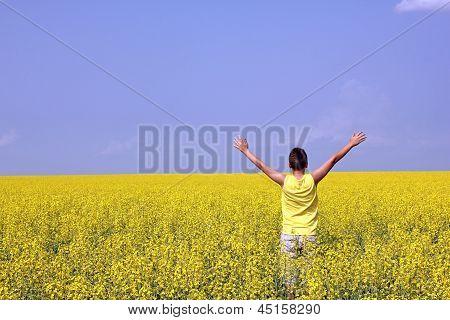 Adolescente feliz, estando em um campo de colza