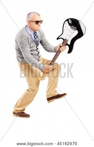 Full length portrait of an angry mature man breaking an electric guitar isolated on white background