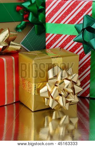 Closeup of an assortment of Christmas presents of varying size on a reflective surface. Vertical Format