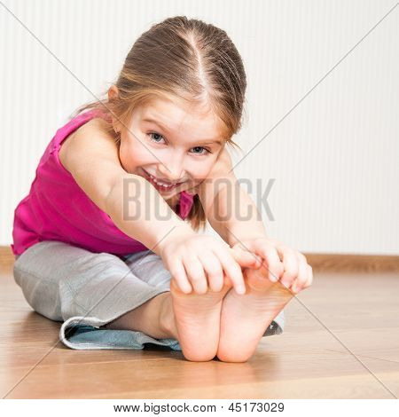 smiling little girl in pink engaged in fitness
