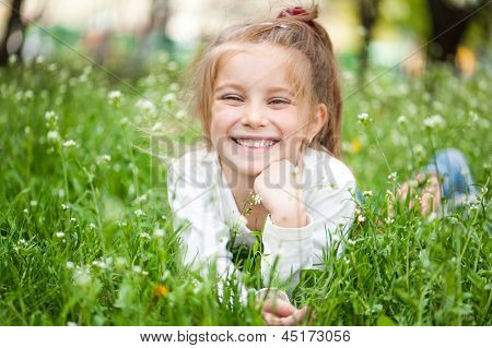 adorable little girl on the meadow in solar summer day
